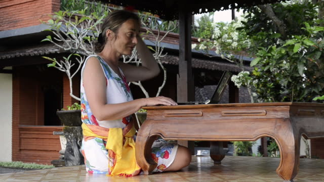 MS Woman is sitting in garden pavilion and putting Hibiscus flower in her hair and using laptop / Ubud, Bali, Indonesia