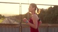 SLO MO vrouw joggen over een snelweg viaduct in de zonsondergang