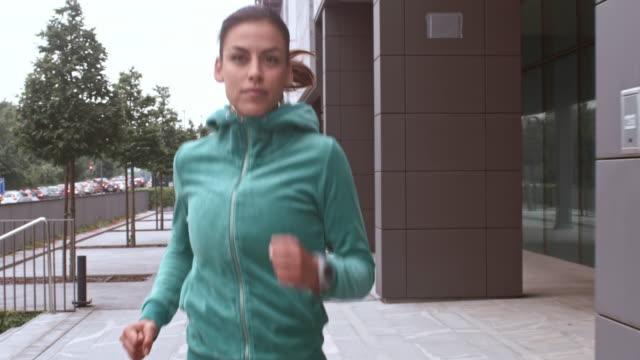 SLO MO TS donna jogging lungo una strada di città