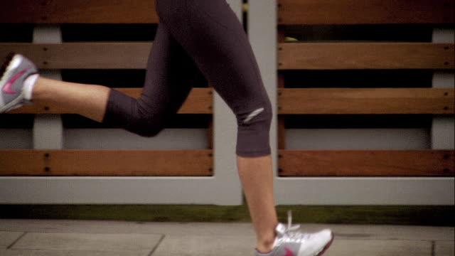 WS TU TS Woman jogging and checking sport band / Portland, OR, USA