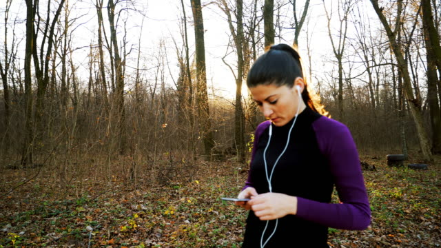 Woman jogging and using the smart phone.