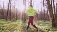 SLO MO TS Woman jogging in a forest on a beautiful spring day