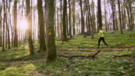SLO MO Woman jogging in a spring forest on a beautiful sunny day