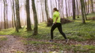 SLO MO TS Woman jogging in a spring forest on a beautiful sunny day