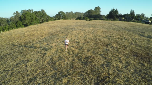 AERIAL CU woman jogging in dry field in suburbs