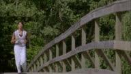 SLO MO MS PAN Woman jogging on wooden footbridge, Ryd, Smaland, Sweden