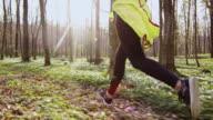 SLO MO TS vrouw joggen door een bos op een mooie lentedag