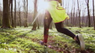 SLO MO TS Woman jogging through a forest on a beautiful spring day