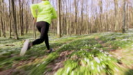 SLO MO TS Woman jogging through a forest