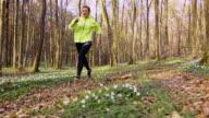 SLO MO  Woman jogging through a spring forest