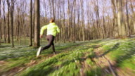 SLO MO TS Woman jogging through a spring forest