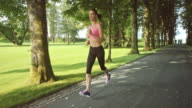 SLO MO TS Woman jogging through a tree-lined lane listening to music