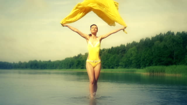Woman jumping in water holding yellow scarf