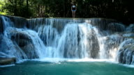 woman jumping into a waterfall