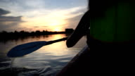 Woman kayaking on the lake in twilight