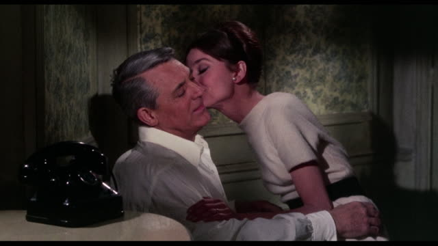 Woman (Audrey Hepburn) kisses man (Cary Grant) affectionately while declaring her love, before the phone buzzes