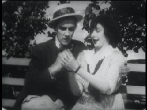B/W 1915 woman kisses man, he puts engagement ring on her finger, they kiss ring + each other