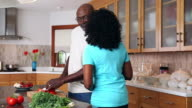 Woman kissing smiling African American man chopping tomato in domestic kitchen