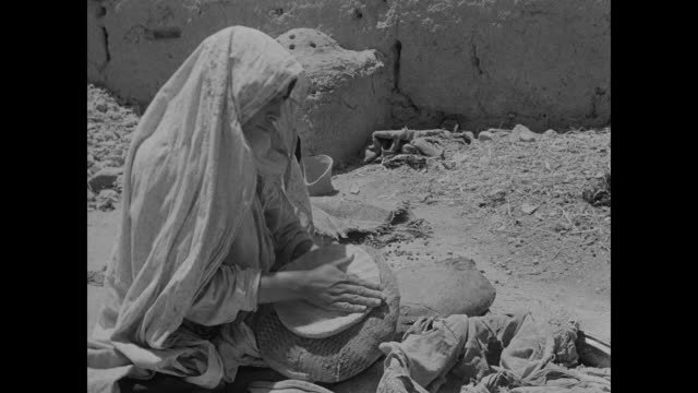 Woman kneading dough on stone placing bread own into outdoor stone oven