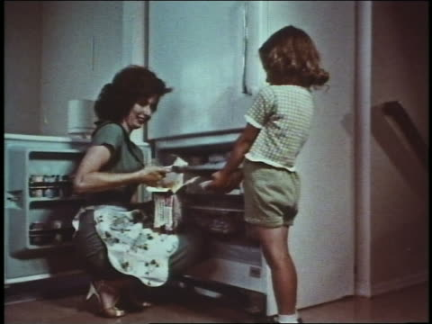 1960 woman kneeling by open freezer scooping ice cream from box for girl with bowl