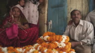 WS Woman knitting at flower vendor stall / Delhi, Delhi , India