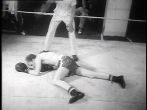 1939 MONTAGE Woman knocking out man in a boxing match / New York City, New York