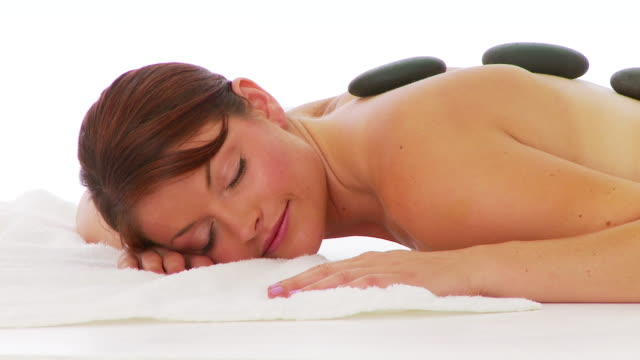 Woman laying facedown at spa with hot rocks on back