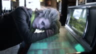 MS Woman laying head on jukebox in old American Diner / Palmdale, CA, United States