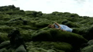 Woman laying on moss covered rock stares up at the clouds
