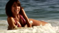 Woman laying on sandy beach with waves