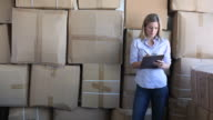 'MS Woman leaning against wall of boxes taking notes on  clipboard in warehouse and look into camera / Brooklyn,New York,United States'