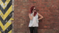 Woman leaning on brick wall talking on cell phone