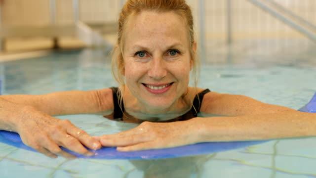 Vrouw leunt op noodle float in zwembad