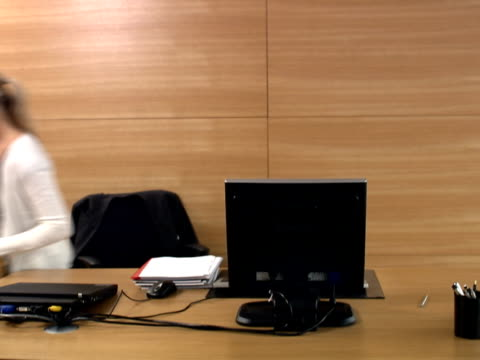 Woman leaves paper on a desk under the desk a man is having problems with the electric flexes Sweden.