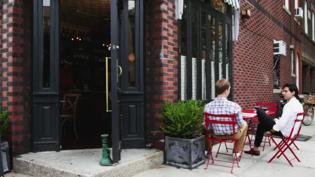 Woman leaving cafe and greeting men as she passes