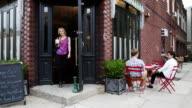 Woman leaving coffee shop, men sitting outdside