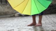 Frau Beine in Regen mit bunten Regenschirm