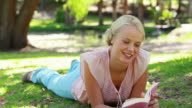 A woman lies down in the park reading as she then looks at the camera