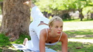 A woman lies on a mat performing a yoga position as she looks at the camera