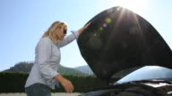 Woman lifts front hood of car, checks engine compartment