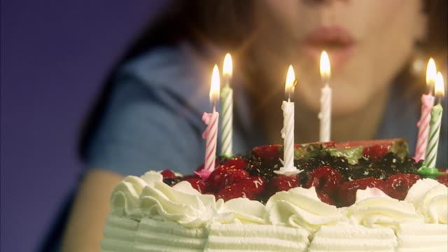 Woman lightening a birthday cake, Sweden.