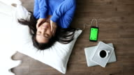 Woman listening to music on the floor by smart mobile with book, coffee cup and Laptop, Green screen, 4k(UHD)