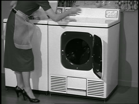 B/W 1953 woman loading dryer with laundry from washing machine / industrial