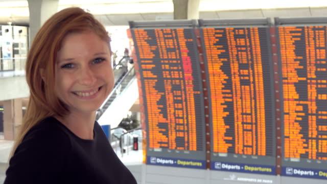 Woman looking at airplane flight information board at airport