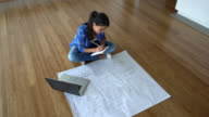Woman looking at blueprints of her new apartment and taking notes