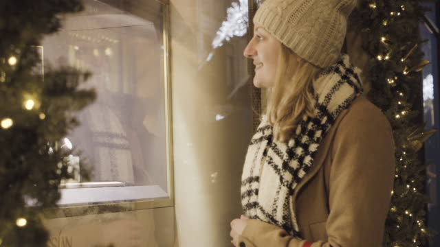 Woman looking at jewelry in shopwindow, doing christmas shopping.