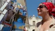 Woman looking at postcards of Capri outside Church of Santa Sofia / Capri