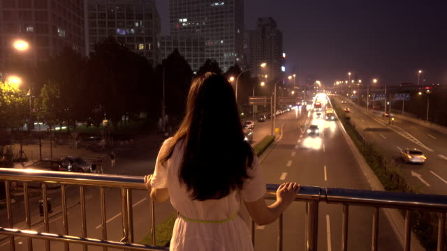 http://media.gettyimages.com/videos/woman-looking-out-city-at-night-video-id483179454?s=640x640