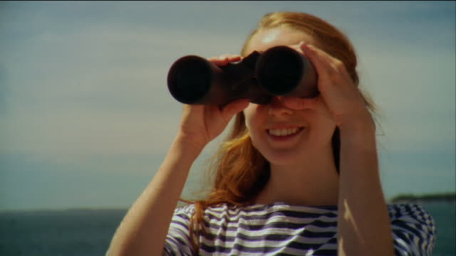 SM CU Woman looking through binoculars and smiling with sea in background / Vinalhaven, Maine, USA