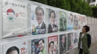 A woman looks at campaign posters of South Korean presidential candidates displayed on a wall in Incheon South Korea on Monday May 8 A woman looks at...